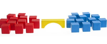 bl: Two groups of blocks in different colors on opposing sides of the image, a bridge in the center connecting the groups.  Blocks made from wood, zoom in closely to see details and imperfections in larger sizes. Shallow depth, focus is in the two leader bl