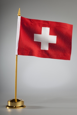 Swiss flag on a grey background  with center spot light on the background