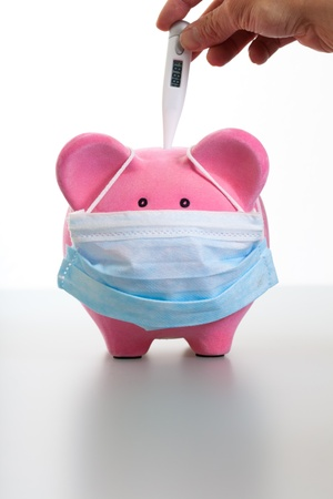 Pink piggy bank wearing a protective face mask  Hand holding a thermometer to measure temperature or feaver Concept for protection, flu, virus, sickness
