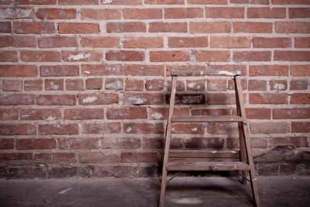 Kleine hölzerne Leiter stehend vor einem rot-Mauer Leichte Sepia-und Vignettierung leer
