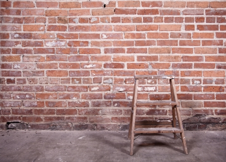 redbrick: Small wooden ladder standing empty in front of a red-brick wall Slight sepia-toned and vignetting