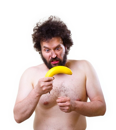 Wild, undressed man with crazy hair and beard, holding a banana in his hands  Studio shot, isolated on white ground. Stock Photo