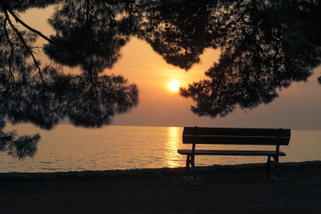 mediterrean: Nobody sitting on an bench at the Mediterrean Sea in Croatia at sunset. Stock Photo