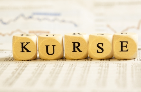 Concept of dices with letters forming word: Kurse - German for stock values. On generic newspaper background with stock market numbers and some blurred charts.  Dices made from wood with natural imperfections.
