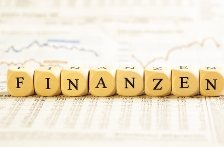 finanzen: Concept of dices with letters forming word: Finanzen - German for Financials. On generic newspaper background with stock market numbers and some blurred charts.  Dices made from wood with natural imperfections. Stock Photo