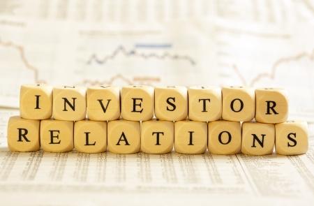 単語を形成する文字とサイコロの概念: 株主・投資家。株式市場の数字といくつかの一般的な新聞背景にぼやけのグラフを実行します。サイコロ自然 写真素材