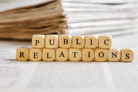relations publiques: Concept de d�s avec des lettres formant des mots: Relations publiques. Fond journal g�n�rique avec un texte flou sur le fond et pile de papier dans le dos. D�s en bois avec des imperfections naturelles.