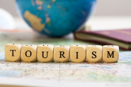 Concept of dices with letters forming words: Tourism. Blurred map, globe and passport as background.   Dices made from wood with natural imperfections. Stock Photo