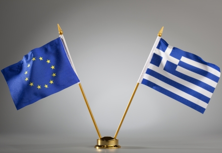 EU and Greek flag on a grey background (with center spot light on the background).