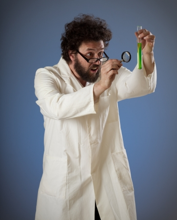 Scientist with weird haird and beard studying some weird fluid in an experimental tube with his loupe.  Self portrait, shot in studio on blue background.. Stock Photo