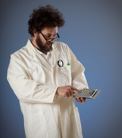 Scientist with weird haird and beard looking confused on his calculator while typing something.