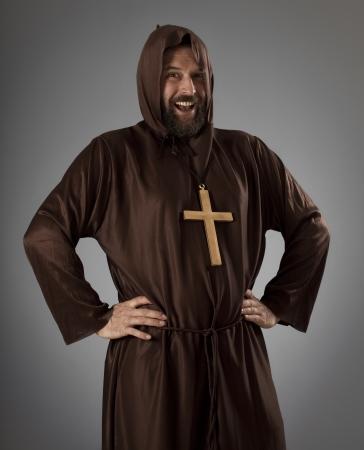 Studio-opname van een licht overgewicht man een monnik gewaad dragen, lachen terwijl kijken naar de camera