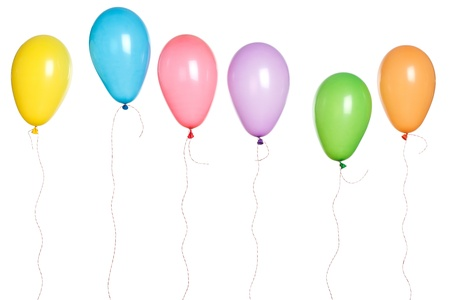 Row of party balloons hanging in the air.  Photographed in studio isolated on white background.