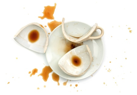 Broken cup with spilled coffee, isolated on white background. Stock Photo