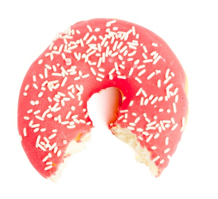 Single red sugar coated doughnut with sprinkles  Half eaten, bites missing Isolated on white background  Stock Photo