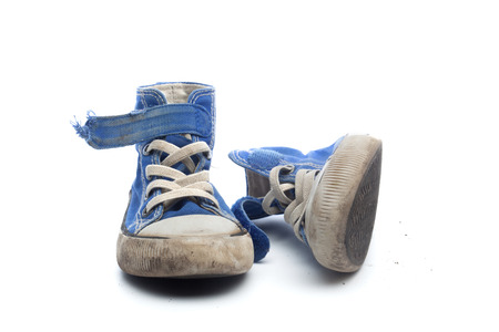 Pair of dirty, worn out blue sneakers in children size, isolated on white background. photo