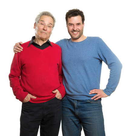 Two Caucasian men, a mature adult around 40 years and a senior, in red and blue pullovers. Generation portrait, father and son. Isolated on white background. photo