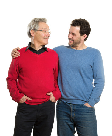 pullovers: Two Caucasian men, a mature adult around 40 years and a senior, in red and blue pullovers. Generation portrait, father and son. Isolated on white background.