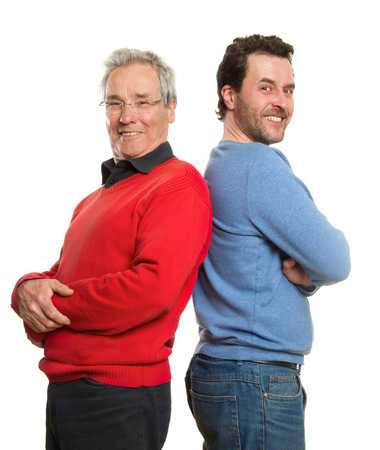Two Caucasian men, a mature adult around 40 years and a senior, in red and blue pullovers. Generation portrait, father and son. Isolated on white background.