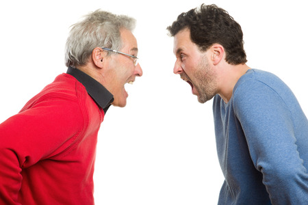 Two Caucasian men screaming at each other. Mature adult around 40 years and a senior, in red and blue pullovers. Generation portrait, father and son. Isolated on white background.