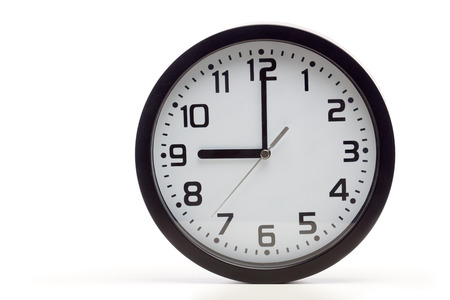 Analog clock with black frame, showing 9 oclock as typical start of working hours.  Cutout, studio shot, isolated on white background.
