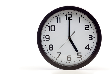 Analog clock with black frame, showing 5 oclock as typical end of office hours.  Cutout, studio shot, isolated on white background. Stock Photo