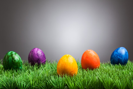 Decoration with grass and colored easter eggs in front of gray background.