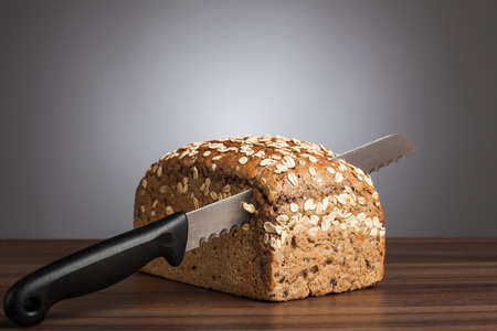 Loaf of wholemeal bread with cutting knife on table in front of gray background.
