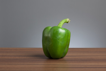 Raw green pepper, vegetable. On table, gray background. Stock Photo