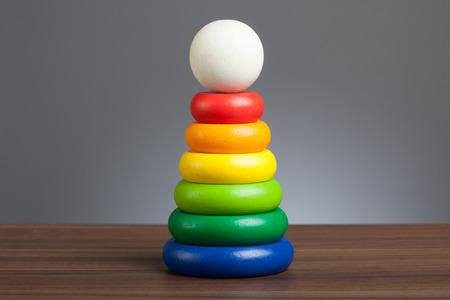 fondo para bebe: Anillos con m�ltiples colores, juguete de madera para beb�s y ni�os peque�os. En la mesa, fondo gris. Foto de archivo