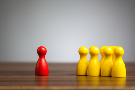 Concept for isolation, mobbing, confrontation: Single red toy pawn figure in opposition to a group of yellow figures.