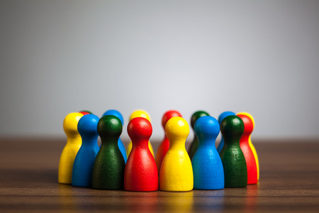 Group, circle of friends, diversity, united concept.  Toy pawn figures on table in front of grey background. Stock Photo