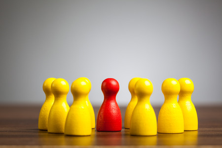 Leadership concept: Red toy pawn figure in the center of a circle group of yellow people. Stock Photo