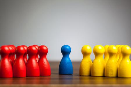 Blauwe figuur in het midden tussen rood en geel groepen. Meditatie, leiderschap, diversiteit, eenwording concept.