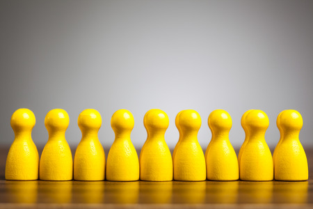 unified: Unified pawn figurines, concept for success and achievement in business teams. On table in front of gray background. Stock Photo
