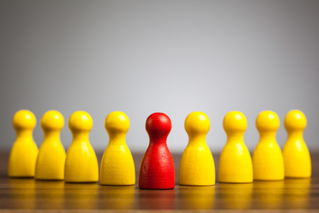Leadership concept: Red toy pawn figure in front of a group of yellow people.