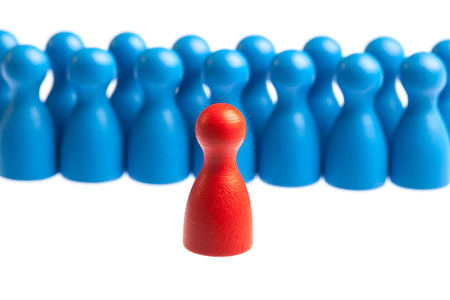 Red pawn standing in front of group of blue figures. Leadership, management concept.  Cutout, isolated on white.