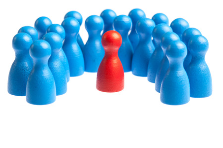Unique red pawn centered in the middle of a large group. Concept for mobbing, autism, diversity, being different.  Cutout, isolated on white. Stock Photo