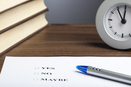 Blue bullet pen, stack of books, clock and an sheet of paper showing Yes No Maybe decision question. Stock Photo