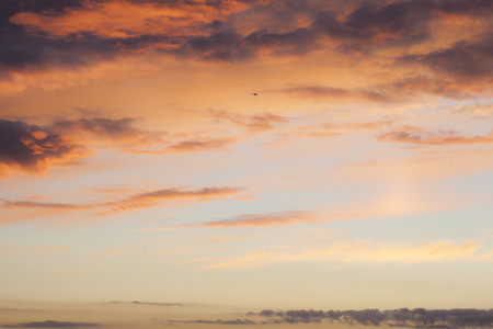 dramatically: Dramatically lit cloudscape in the sky, sunset coloring. And a tiny helicopter silhouette.