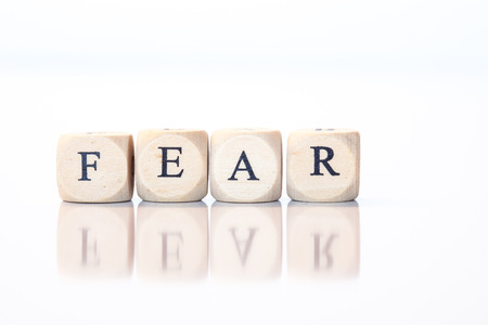 Word Fear spelled from single dice letters, with reflection on bottom