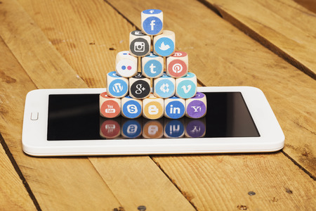 Concept - cubes of internet icons on a tablet computer. Set of dices with logos from most popular social media networks, including Facebook, Google, Instagram, Twitter, Pinterest, LinkedIn and many more