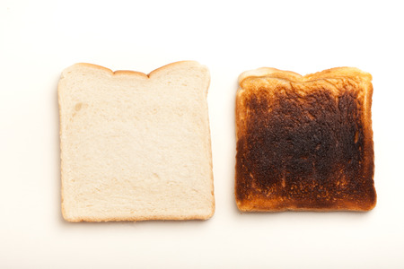 Two slices of bread, one raw, another toasted burnt. Studio shot on white background.