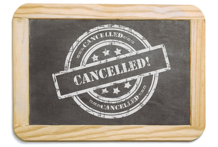 layered: Black board with wooden frame, layered grund design chalk message in stamp form: Cancelled. Isolated on white background. Stock Photo