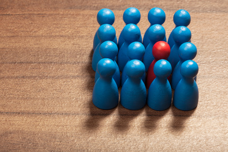 Be different, one red toy figurine among blue pawns. Concept on wood table.