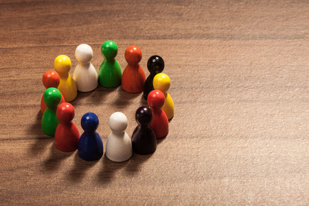 Circle of diversity, friends, colorful toy pawns. Concept on wood table. Stockfoto