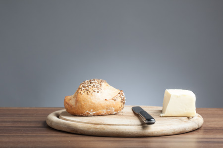 bread roll: Breakfast plate with knife, wholemeal bread roll with carawy seeds and a piece of butter. Stock Photo