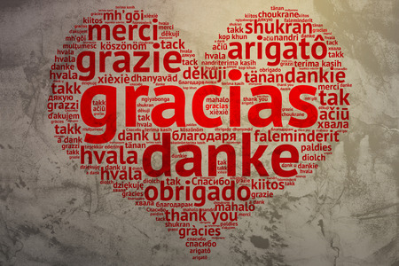 metadata: Focus on Spanish: Gracias. Word cloud in heart shape on Grunge Background. saying thanks in multiple languages. Stock Photo