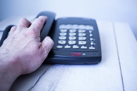 holz: Männliche hat greift nach einem schwarzen Telefonhörer.