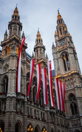 Stil: Beleuchtetes Rathaus in Wien mit Landesflagge und Blumenschmuck in Neogotik von Friedrich von Schmidt, Österreich.